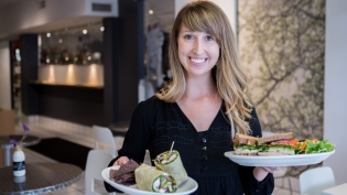 Kyle Orlando serves sandwiches and wraps at Organic 3 Cafe in Snyder, NY